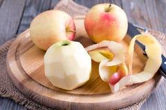 Het pellen van een appel met een mes op een houten achtergrond Royalty-vrije Stock Foto's