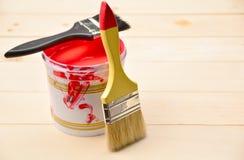 Het penseel en de verf kunnen en met rode kleur op houten lijst stock afbeelding