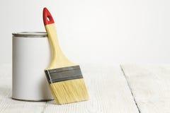 Het penseel en kan, borstel en witte kleur op houten vloer schilderen royalty-vrije stock afbeeldingen