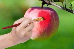 Het penseel schildert rode rijpe appel in tuin royalty-vrije stock fotografie