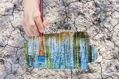 Het penseel schildert watervulklei op droge aarde Stock Afbeeldingen