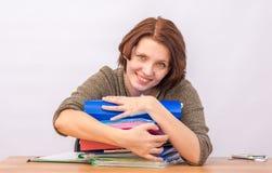 Het personeel die van het meisjesbureau koesterend een stapel omslagen glimlachen stock foto