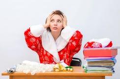 Het personeelslid van het meisjesbureau kleedde zich aangezien Santa Claus zijn hoofd bij zijn bureau grijpt Stock Foto