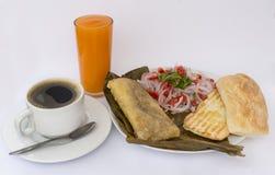 Het Peruviaanse ontbijt riep Tamal gekookt graan dat met kip wordt gemengd en dat in graanbladeren wordt verpakt ` Criolla salade stock foto