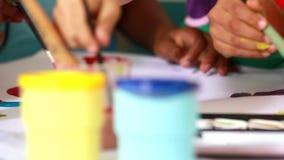 Het peuterklasse schilderen bij lijst in klaslokaal stock footage