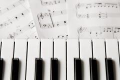 Het pianotoetsenbord blured muziek-nota's achtergrond stock foto