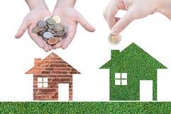Het pictogram van het de holdingshuis van de muntstukhand in aard als symbool van hypotheek Royalty-vrije Stock Foto's