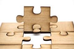 Het plaatsen missend een stuk van raadsel het bedrijfsconcept, stukken wordt van houten figuurzaag verbonden samen ge?soleerd op  stock foto's