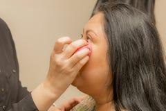 Het plaatsen van de basis van de make-up in een professionele make-up stock foto