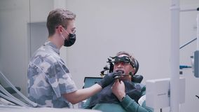 Het plaatsen van de kaak van de patiënt in de tandkliniek stock video