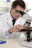 Het plaatsen van dia onder microscoop stock foto