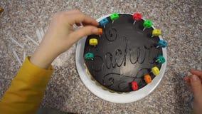 Het plaatsen van kaarsen op de cake, verjaardag stock footage