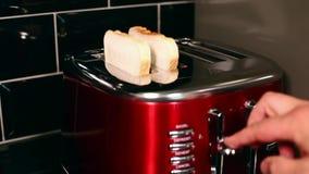 Het plaatsen van twee plakken van toostbrood in de Broodrooster stock videobeelden