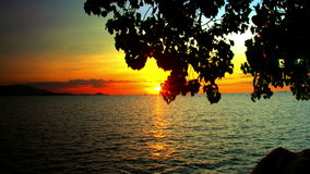 Het plaatsen van zon over golvende water en silhouetten van stock videobeelden