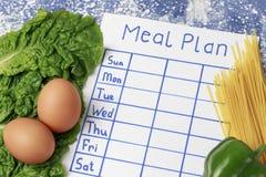 Het Plan van de inschrijvingsmaaltijd, programma op wit blad en salade Mening van hierboven royalty-vrije stock afbeeldingen