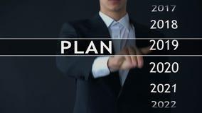 Het plan voor 2021, zakenman kiest dossier op het virtuele scherm, startstrategie stock videobeelden
