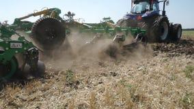 Het planten van de lente Sluit omhoog van tractor met ploeg die en gebied zaaien cultiveren stock videobeelden