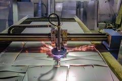 Het plasma sneed machine met de scherpe staalplaat van de programmacontrole met vonken in metaalbewerkingsfabriek stock afbeelding