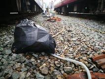 Het plastic die afval doet Zwarte in zakken tussen treinen bij de post wordt geplaatst royalty-vrije stock foto