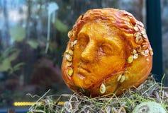 Het plastische hoofd is gesneden van een oranje pompoen stock afbeelding