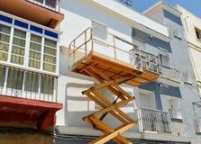 Het platform van de schaarlift voor het schilderen van de voorgevel van een huis Stock Afbeeldingen