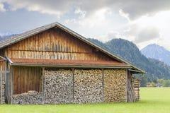 Het platteland van Duitsland met oud die chalet, met voorraad van houten logboeken klaar voor gebruik wordt ingepakt royalty-vrije stock fotografie