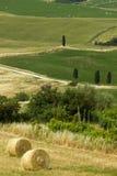 Het platteland van TOSCANIË met landbouwbedrijven en hooi-bal stock foto's