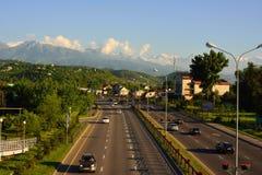 Het plattelandscityscape van Alma Ata met bergen en weg Stock Fotografie