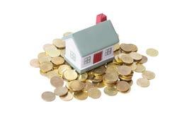 Het plattelandshuisje dat van het stuk speelgoed zich op een hoop van muntstukken bevindt. Stock Afbeelding