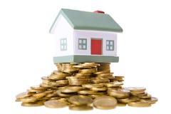 Het plattelandshuisje dat van het stuk speelgoed zich op een hoop van muntstukken bevindt. Stock Afbeeldingen