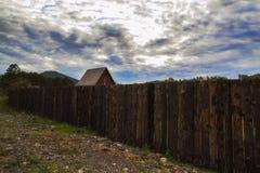 Het plattelandshuisje door de oude houten omheining in het dorp op dark betrekt achtergrond Royalty-vrije Stock Afbeeldingen