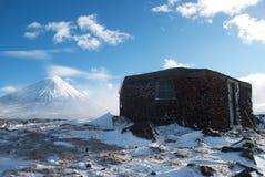 Het plattelandshuisje van de steen in de sneeuwbergen Stock Afbeelding