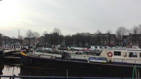 Het plein van Amsterdam op zonsondergang met mensen stock fotografie