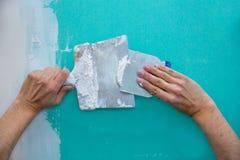 Het pleisteren van mensenhanden met plaste op drywall gipsplaat Royalty-vrije Stock Fotografie