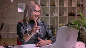 Het plezierige gelukkige blonde Kaukasische meisje toont aan als teken terwijl het zitten van dichtbij haar laptop een Desktop en stock videobeelden