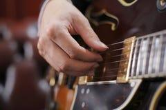 Het plukken van de gitaar Stock Foto's