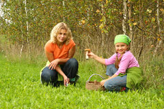 Het plukken van de moeder en van de dochter paddestoelen stock afbeelding
