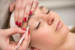 Het plukken van wenkbrauwen met tweezer door schoonheidsspecialist in schoonheidssalon Stock Foto's