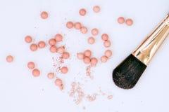 Het poeder in de ballen met een stralend effect op de achtergrond van de reeks voor bloost Samenstellingsschoonheidsmiddelen, stock foto's