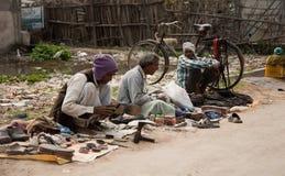 Het poetsmiddel van de laars bij straat Stock Foto's