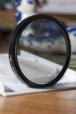 Het polariseren van CPL-filter voor de lens op de lijst in een open vakje stock afbeelding