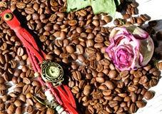 Het polshorloge en droogt de roze Knop op de koffieboon stock foto's