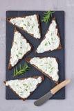 Het pompernikkelbrood met feta, de roomkaas, de rozemarijn, de citroen en het knoflook dompelen, op een leiraad, hoogste vertical Royalty-vrije Stock Foto's