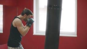 Het ponsen in dozen doende zak van de sportmens bij opleiding Kickboxer opleiding in strijdclub stock videobeelden