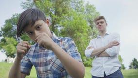 Het ponsenlucht die van de portret aanbiddelijke jongen in de camera in het de zomerpark kijken Zijn vader die van oudere broer z stock video