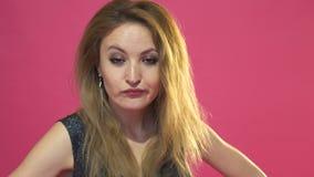 Het portret de jonge mooie vrouw met een vuist bedreigt is geïsoleerd op roze stock footage
