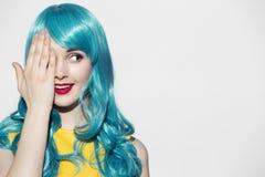 Het portret die van de pop-artvrouw blauwe krullende pruik dragen Stock Foto's