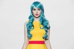 Het portret die van de pop-artvrouw blauwe krullende pruik dragen royalty-vrije stock afbeelding