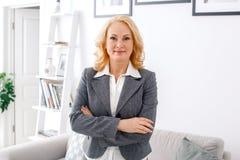 Het portret die van de vrouwenpsycholoog zich bij de toevallige gekruiste wapens van het huisbureau bevinden royalty-vrije stock afbeeldingen