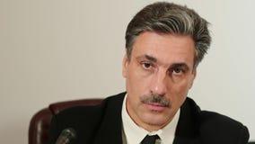 Het portret een mens bij een persconferentie beantwoordt de vragen van journalisten stock video